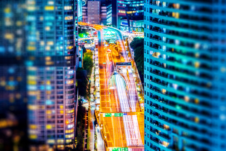 Asia business concept for real estate and corporate construction - panoramic urban city skyline aerial night view with highway in hamamatsucho, tokyo, Japan with tilt shift, miniature, blur effect