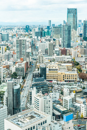 Asia Business concept for real estate and corporate construction - urban city skyline aerial view under bright blue sky and sun in Tokyo, Japan