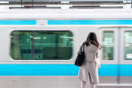 Asia Business concept for real estate and corporate construction - Asia business woman with blurry moving train in background in Tokyo, Japan