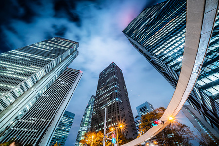Asia Business concept for real estate and corporate construction - looking up night view in road intersection of shinjuku, the skyscrapers reflect twilight sky in Tokyo, Japan Archivio Fotografico