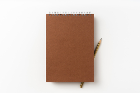 Design concept - Top view of brown spiral notebook, white page and pencil isolated on background for mockup 免版税图像