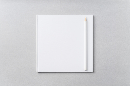 Design concept - Top view of pure white notebook, white page and pencil on grey background for mockup