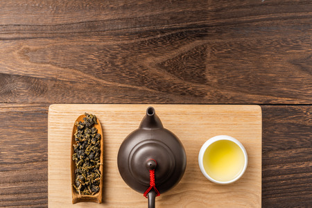 Asia culture and design concept - man's hand hold fresh taiwan oolong tea and teapot on dark wood background