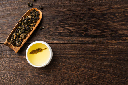 Asia culture and design concept - fresh taiwan oolong tea and cup on dark wood background Stock Photo