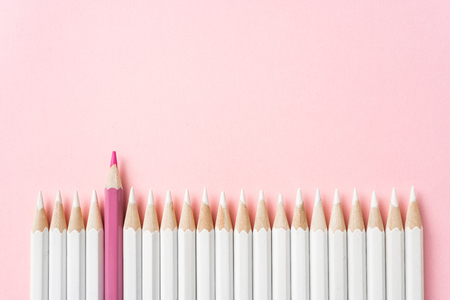 Business and design concept - lot of white pencils and one color pencil on pink paper background. It's symbol of leadership, teamwork, success and unique. Banque d'images