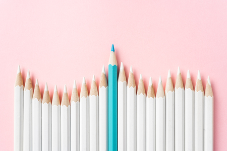 Business and design concept - lot of white pencils and one color pencil on pink paper background. It's symbol of leadership, teamwork, success and unique. Stock Photo