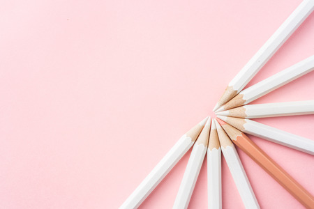 Business and design concept - lot of white pencils and one color pencil on pink paper background. It's symbol of leadership, teamwork, success and unique. Banco de Imagens