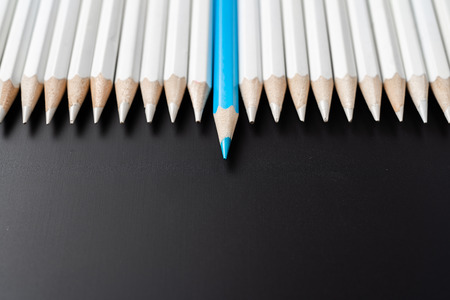 Business and design concept - lot of white pencils and one color pencil on black background. Its symbol of leadership, teamwork, success and unique.