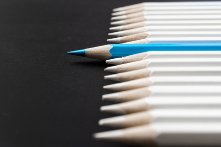 Business and design concept - lot of white pencils and one color pencil on black background. It's symbol of leadership, teamwork, success and unique.