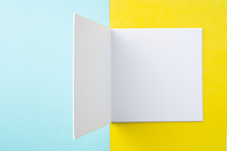 Design concept - Top view of opening square white notebook on colorful yellow and blue background for mockup