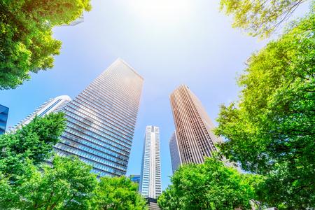 Azië Bedrijfsconcept voor onroerend goed, bedrijfsbouw en ecologie - uitzicht op de panoramische moderne skyline van de stad met blauwe lucht en groene boom in shinjuku, tokyo, japan opzoeken Stockfoto
