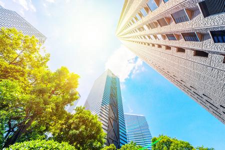 Concepto de negocio de Asia para bienes raíces, construcción corporativa y ecología - mirando hacia arriba la vista del horizonte de la ciudad moderna panorámica con cielo azul y árbol verde en shinjuku, tokio, japón