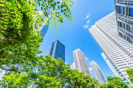 Asia Business concept for real estate, corporate construction and ecology - looking up view of panoramic modern city skyline with blue sky and green tree in shinjuku, tokyo, japan Banque d'images - 119139252