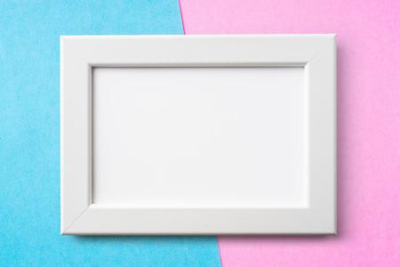 Design concept - white wood frame on blue and pink paper background for mockup