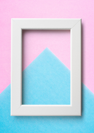 Design concept - white wood frame on blue and pink paper background for mockup
