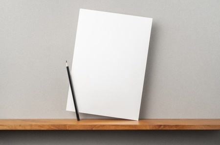 Design concept - front view of A4 hard paper stand on bookshelf and grey wall for mockup