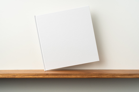 Design concept - front view of square white notebook on bookshelf and white wall for mockup