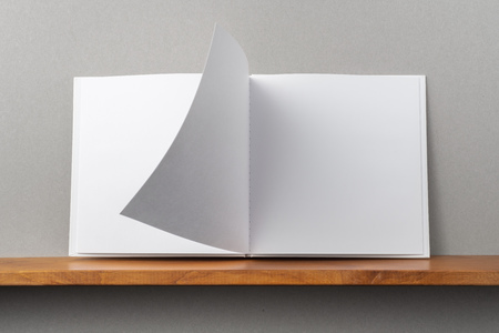 Design concept - front view of opened square white notebook on bookshelf and grey wall for mockup