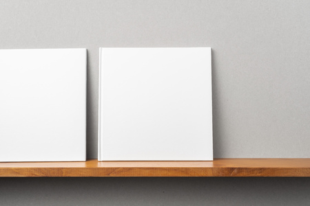 Design concept - front view of 2 square white notebook on bookshelf and grey wall for mockup