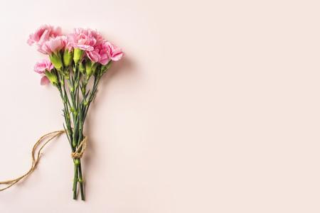 Concetto di design - vista dall'alto un mazzo di garofani con corda di canapa su sfondo rosa per il modello della festa della mamma