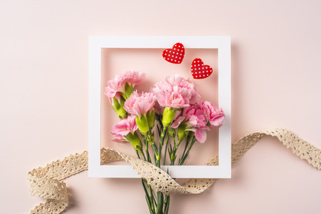 Design concept - top view of carnation with white square frame and heart shape and vintage ribbon decoration on pink background for mother day mockup