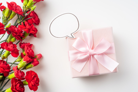 event design concept - top view of a bunch of red carnation, talk frame and gift box isolated on white background for mothers day and valentines day, wedding event with copy space for mock up Stock Photo