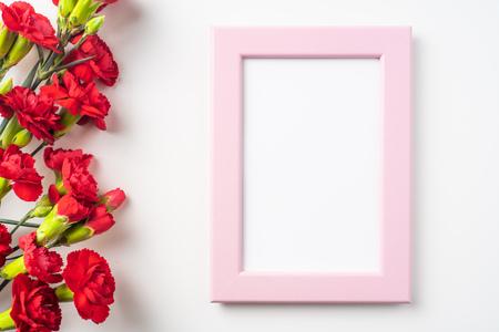 事件设计概念 - 一束的顶视图红色康乃馨和桃红色照片框架隔绝的在白色背景为母亲节和情人节,与拷贝空间的婚礼事件嘲笑的婚礼事件