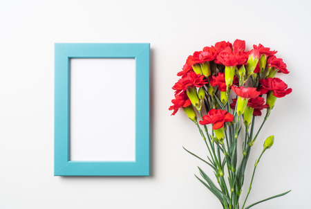 event design concept - top view of a bunch of red carnation and photo frame isolated on white background for mothers day and valentines day, wedding event with copy space for mock up