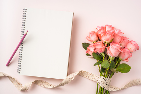event design concept - top view of a bunch of pink rose , gift box , white page and vintage ribbon on pink background for mothers day and valentines day, wedding event with copy space for mock up