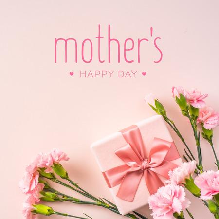 concept de conception d'événement - vue de dessus d'un bouquet d'oeillets roses avec boîte-cadeau et mot de salutation sur fond rose pour l'événement de la fête des mères avec espace de copie pour la maquette