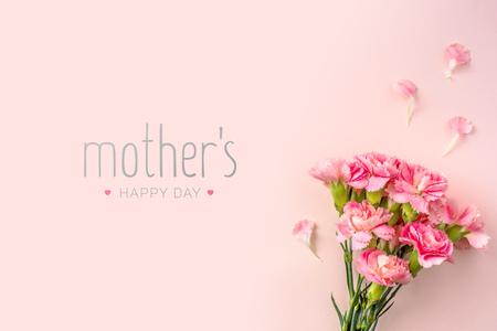 Concepto de diseño de eventos: vista superior de un manojo de clavel rosa con palabra de saludo sobre fondo rosa para el evento del día de la madre con espacio de copia para maqueta