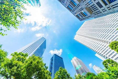 亚洲地产、企业建设和生态的商业理念——在日本东京新宿仰望现代城市全景,蓝天绿树