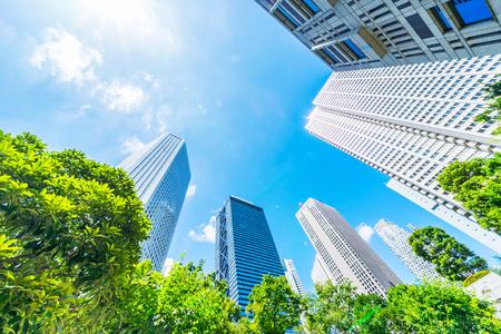 Azja Koncepcja biznesowa dla nieruchomości, budownictwa korporacyjnego i ekologii - patrząc w górę na panoramiczną panoramę nowoczesnego miasta z niebieskim niebem i zielonym drzewem w shinjuku, tokio, japonia