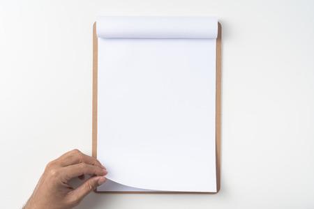 Concept de design - vue de dessus de l'homme main tenir du papier A4 blanc retourné sur un presse-papiers marron isolé sur fond blanc pour la maquette. vraie photo, pas de rendu 3D Banque d'images
