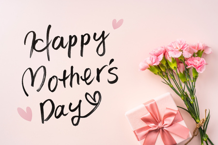 mothers day design concept - top view of a bunch of carnation, gift box, hand writing script on pink background with copy space for mock up