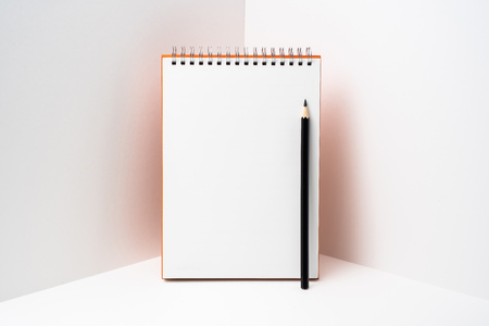 Spiral notebook with black colored pencil on white space