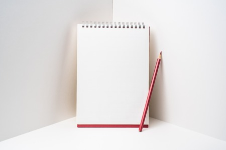 Spiral notebook with red colored pencil on white space Reklamní fotografie