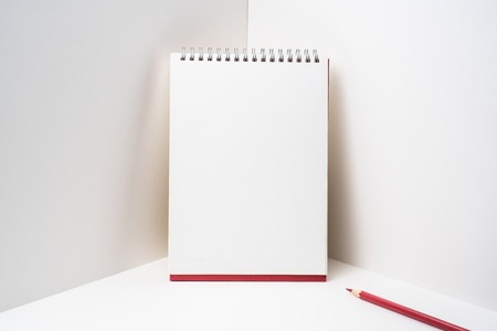 Spiral notebook with red colored pencil on white space 免版税图像