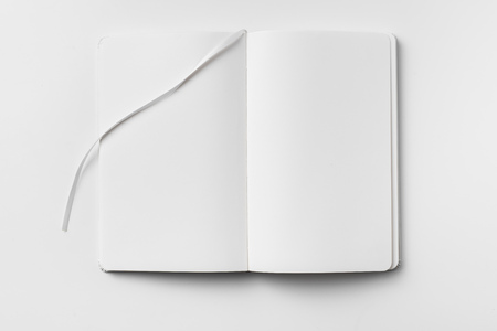 Design concept - top view of open white notebook with blank page and ribbon bookmark isolated on white background for mockup. real photo, not 3D render Фото со стока
