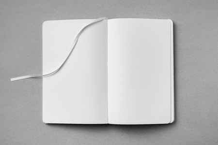 Top view of open white notebook with blank page and ribbon bookmark on grey background
