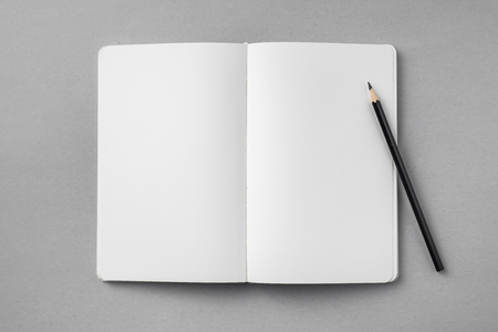 Top view of open white notebook with blank page and wooden pencil on grey background