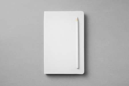 Top view of white notebook with wooden pencil on grey background