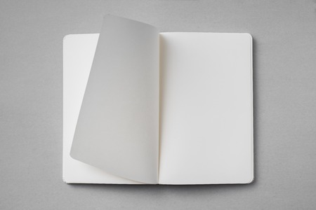 Top view of blank flipped paper on white notebook isolated on grey background