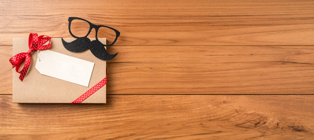 event design concept - top view of fathers day layout with red ribbon & kraft gift box, silhouette of eye glasses and beard, copy space for mock up