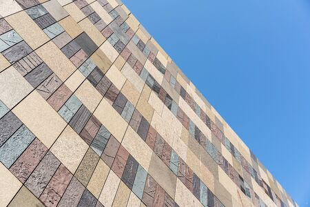 looking up view of stone tile ceramic brick wall background against blue sky