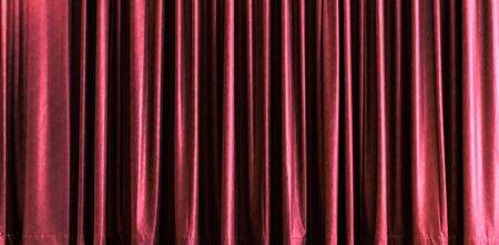 Design material - red closed stage curtain with light effect in a theater