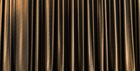 Design material - golden closed stage curtain with light effect in a theater