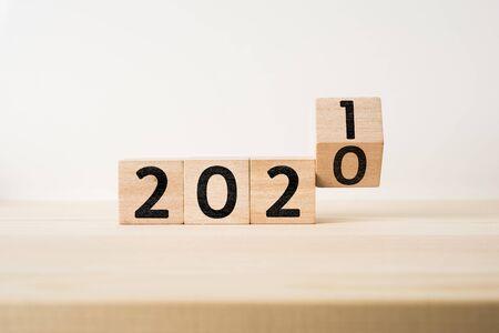 Geschäfts- und Designkonzept - surrealer abstrakter geometrischer schwimmender Holzwürfel mit Wort 2021 und 2020 Konzept auf Holzboden und weißem Hintergrund Standard-Bild