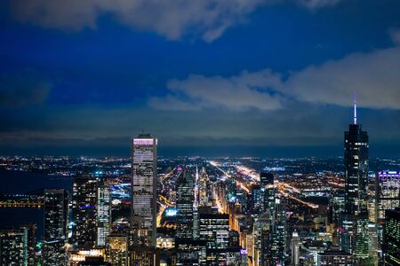 Business concept for real estate and corporate construction - panoramic urban city skyline aerial view under twilight sky and beautiful night in Chicago, America