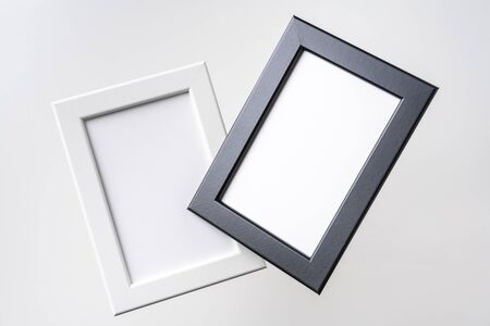 Design concept - top view of two black and white wood photo frame float on mid air isolated on white background for mockup, real photo, not 3D render